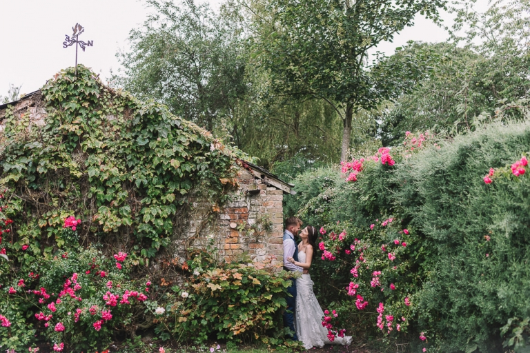 an ivy covered building with a Lancashire wedding couple leaning against it