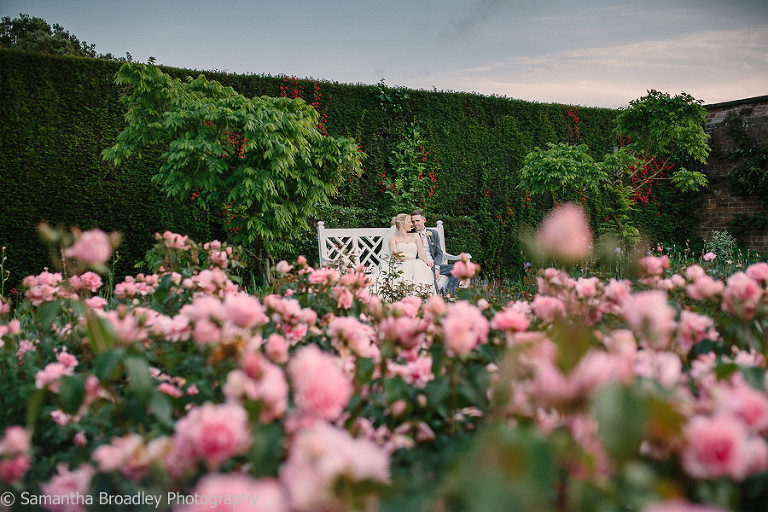 Sitting amongst the roses of Arley Hall on their Wedding Evening